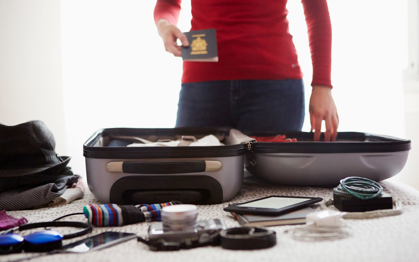 Woman packing suitcase, holding passport, mid section
