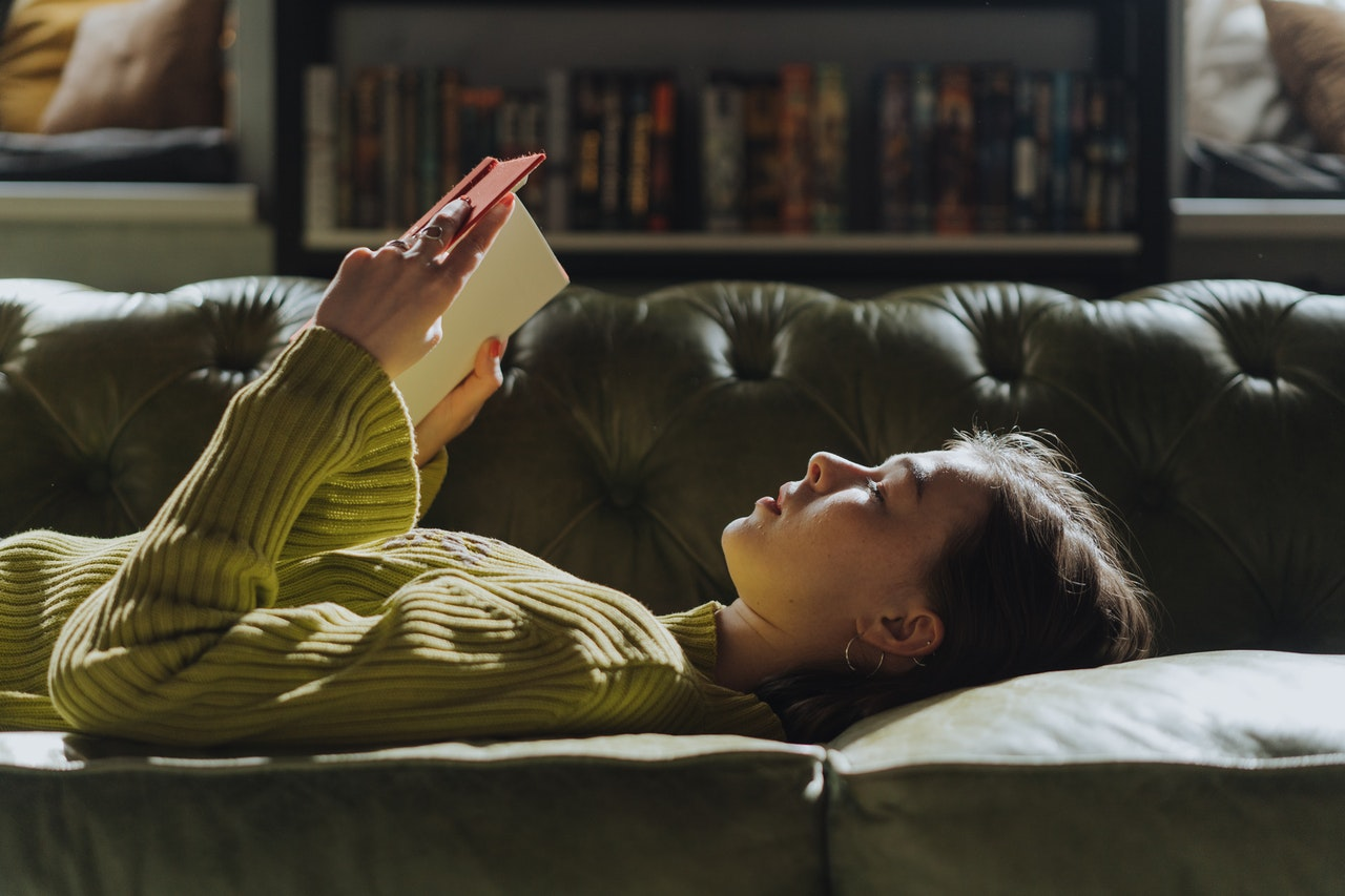 woman reading book lying on bed
