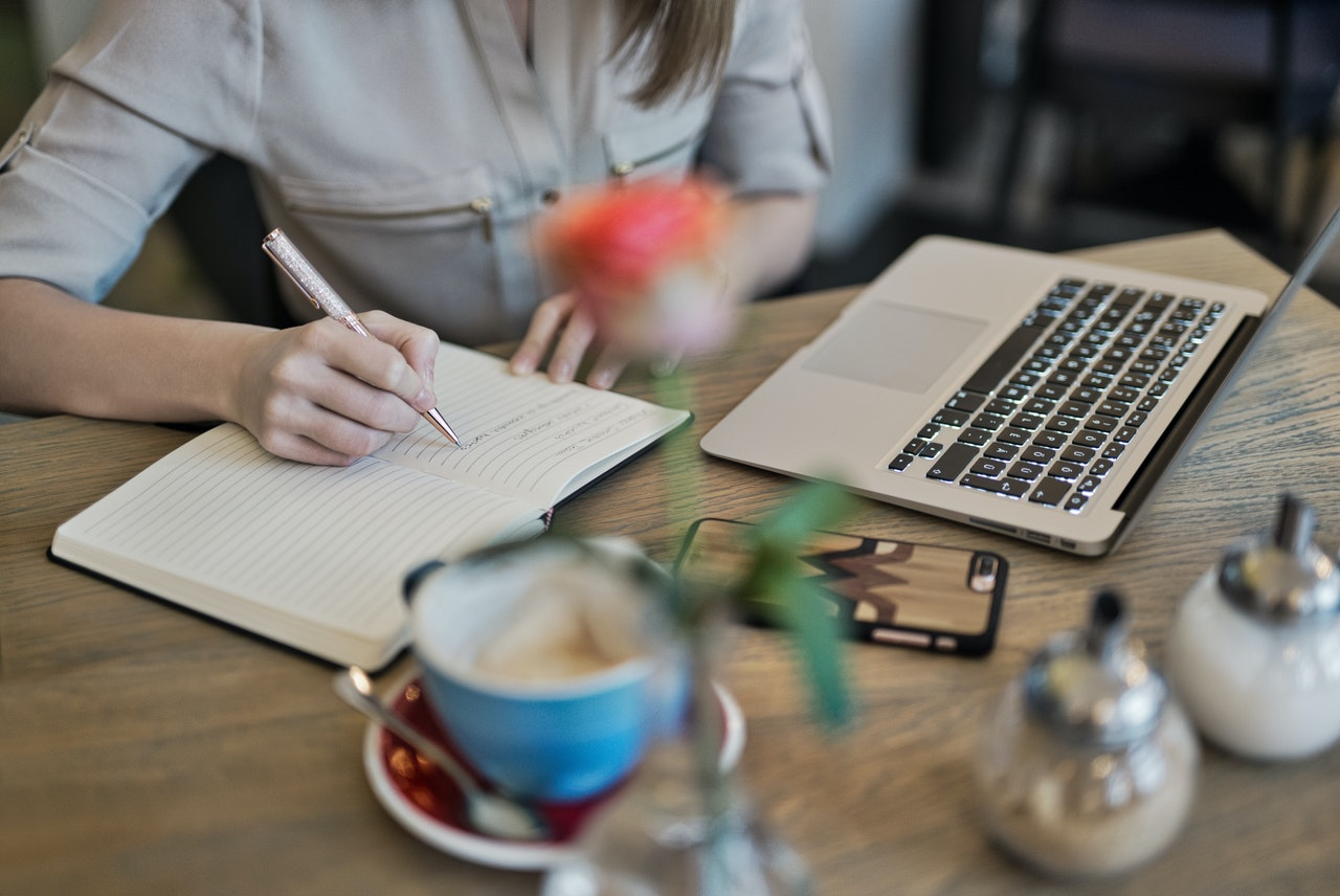 woman writing in front of laptop