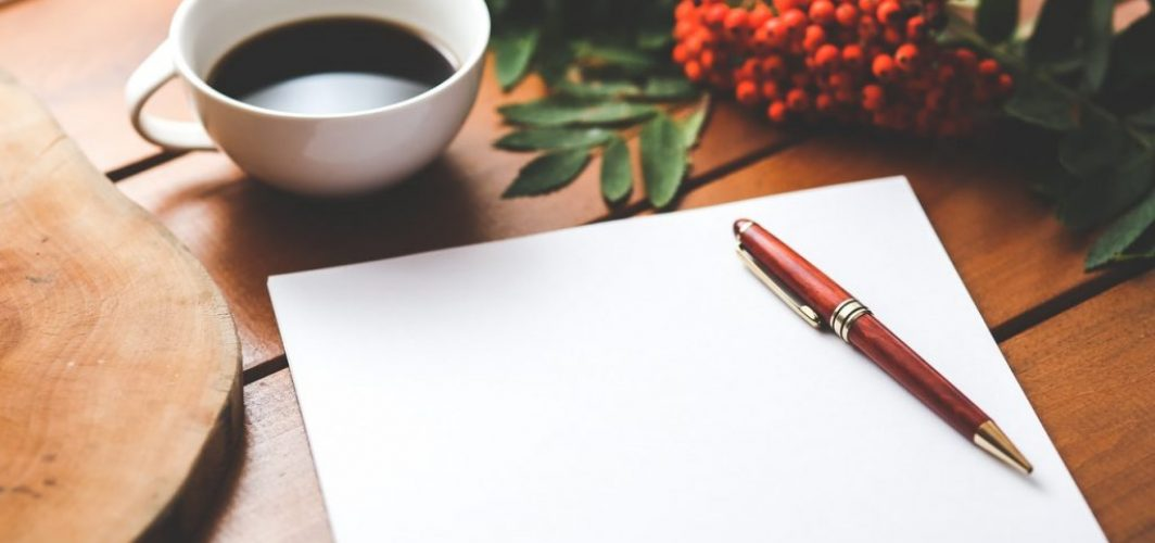 coffee, paper and pen on table for writing